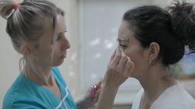 Nahaufnahme-Kosmetiker wendet spezielles Augenpflege-Produkt an der Schönheit für Tätowierung an stock footage