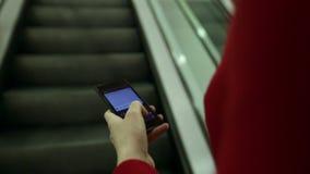Nahaufnahme kurz von der Frau, die auf einem Smartphonegerät beim Rolltreppe weitergehen schreibt stock video
