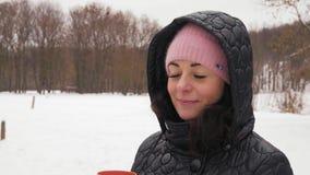 Nahaufnahme-lächelnde Frau in Hood Drinking Hot Coffee im Winter-Wald stock video