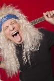 Nahaufnahme männlichen Gitarristen des von mittlerem Alter, der heraus Zunge über farbigem Hintergrund haftet Stockfoto