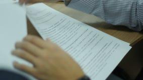 Nahaufnahme-Mann in der Hemd-Drehungs-Seite des Dokuments mit Stift in der Hand stock video footage
