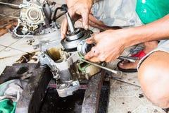 Nahaufnahme, Mann, der Maschinenmotorrad repariert Lizenzfreie Stockfotos