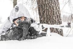 Nahaufnahme-Mannsoldat im Winter auf einer Jagd mit einem Scharfschützegewehr in der weißen Wintertarnung liegt hinter einem Baum stockbilder