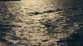 Nahaufnahme, Meereswellen bei Sonnenuntergang, in den Strahlen des weichen Sonnenlichts Greller Glanz auf dem Wasser stock footage