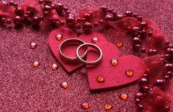 Nahaufnahme mit Unschärfe Roter Hintergrund mit zwei Ringen und einem Herzen, nahe kleinen Glasherzen Ð¯Ð·Ñ ‹Ðº кГ ÑŽÑ-‡ Ð?Ð ²  stockbilder
