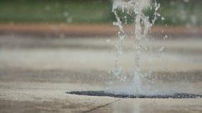Nahaufnahme oben von Kind-` s Füßen, die öffentlich durch Park des Brunnens spielen und laufen Flache Tiefe des Feldes, getontes  stock footage