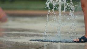 Nahaufnahme oben von Kind-` s Füßen, die öffentlich durch Park des Brunnens spielen und laufen Flache Tiefe des Feldes, getontes  stock video