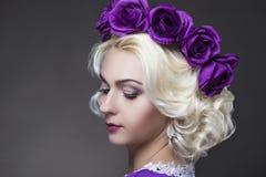 Nahaufnahme-Porträt der blonden Frau einzigartige blumige purpurrote Krone tragend Stockbilder