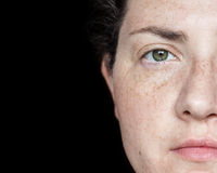 Nahaufnahme-Porträt der Frau mit den Sommersprossen und grünen Augen lokalisiert auf einem schwarzen Hintergrund: Hälfte des Gesi Lizenzfreies Stockbild