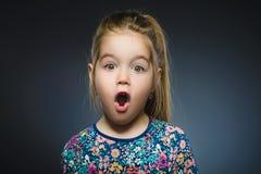 Nahaufnahme-Porträt der gehenden Überraschung des kleinen Mädchens auf grauem Hintergrund lizenzfreies stockbild