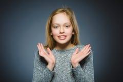 Nahaufnahme-Porträt der gehenden Überraschung des kleinen Mädchens auf grauem Hintergrund Lizenzfreie Stockfotos