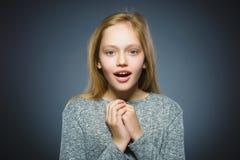 Nahaufnahme-Porträt der gehenden Überraschung des kleinen Mädchens auf grauem Hintergrund lizenzfreies stockfoto