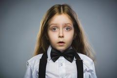 Nahaufnahme-Porträt der wundernden gehenden Überraschung des Mädchens auf grauem Hintergrund Stockfotografie