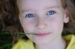 Nahaufnahme-Porträt des weibliches Kindergesichtes mit blauen Augen Nettes kleines Mädchen, das auf dem grünen Gras liegt und bet stockbilder
