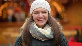 Nahaufnahme-Porträt einer schönen lächelnden jungen Frau, die warme Kleidung trägt Mädchen, welches die Kamera lacht und betracht stock footage