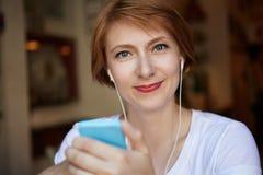Nahaufnahme-Porträt-moderne Hippie-weibliche kurze gelockte Frisur-tragendes weißes modisches T-Shirt, den Spaß habend und betrac stockfotografie