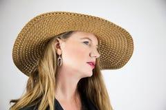 Nahaufnahme-Porträt-reifes blondes weibliches großes Hut-Gesicht gekippt weg von Kamera Stockfoto