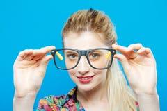 Nahaufnahme-Porträt von lustigen lächelnden Blondinen mit dem Pferdeschwanz, der buntes Hemd und moderne Brillen auf Blau trägt Lizenzfreie Stockfotografie