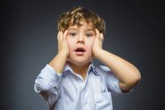 Nahaufnahme-Porträt des hübschen Jungen mit erstauntem Ausdruck bei der Stellung gegen grauen Hintergrund Stockfoto