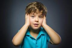 Nahaufnahme-Porträt des hübschen Jungen mit erstauntem Ausdruck bei der Stellung gegen grauen Hintergrund Lizenzfreie Stockfotos