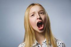 Nahaufnahme-Porträt des hübschen Mädchens mit erstauntem Ausdruck bei der Stellung gegen grauen Hintergrund Stockfotografie