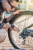 Nahaufnahme-Radfahrer-Mann, der Fahrrad repariert Stockbild