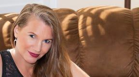 Nahaufnahme-reifes blondes weibliches sitzendes Sofa Lizenzfreies Stockbild