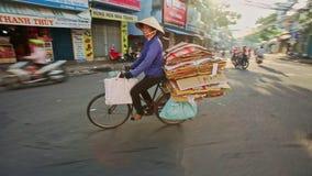 Nahaufnahme-Reiter auf Fahrrad trägt Pappstapel-Drehungen zur Straße stock footage