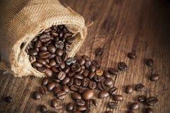 Nahaufnahme rost Kaffeesamen und -sack auf hölzerner Tabelle Stockfotografie