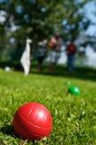 Nahaufnahme roten boccia Balls, der im Gras und in Leuten spielen im Hintergrund liegt lizenzfreie stockfotos