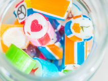 Nahaufnahme am roten Herzen und bunte Zuckerstangen im Glasgefäß Stockfoto