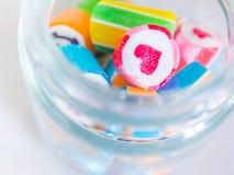 Nahaufnahme am roten Herzen und bunte Zuckerstangen im Glasgefäß Lizenzfreie Stockfotografie