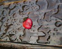 nahaufnahme Rotes Herz auf einem hölzernen Hintergrund mit Regentropfen stockfoto