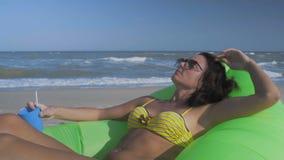Nahaufnahme-Schönheit in der Sonnenbrille stehen auf den Seestrand-Lügen auf einem grünen aufblasbaren Kissen mit Cocktail in der stock video