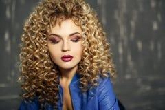 Nahaufnahme-Schönheitsporträt des blonden Mädchens des sexy Kraushaars im Studio mit dunklem Hintergrund lizenzfreies stockfoto
