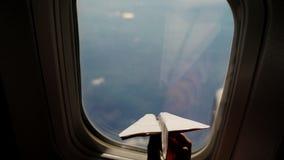 Nahaufnahme Schattenbild einer Kinderhand mit kleiner Papierfläche vor dem hintergrund des Flugzeugfensters Kindersitzen stock video