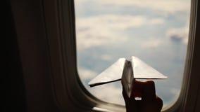 Nahaufnahme Schattenbild einer Kinderhand mit kleiner Papierfläche vor dem hintergrund des Flugzeugfensters Kindersitzen stock footage