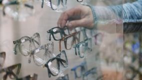 Nahaufnahme, Schaukasten im optischen Speicher, Optik, Einzelhandelsgeschäft des Optikers, Brillen kaufen, viele Gläser, Rahmen,  stock video
