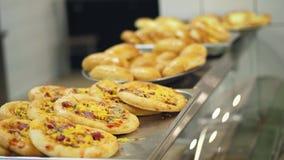 Nahaufnahme, Schaukasten mit Minipizza, Hefeteigbacken in der modernen Kantine, Cafeteria, Selbstbedienungsrestaurant der Öffentl stock video footage