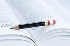Nahaufnahme schoss vom Bleistift auf Seiten des Buches stockfotos