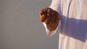 Nahaufnahme schoss vom Porträt und von den Händen jungen arabischen Scheichkerls in der Sandwüste am klaren Sommertag im Freilich stock footage