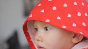 Nahaufnahme schoss von aufpassenden Karikaturen des blauäugigen Babygesichtes Das Kind in der roten Haube mit silbernen Herzen ko stock video