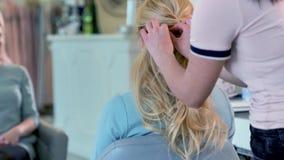 Nahaufnahme schoss von den eleganten Blondinen auf den Schönheitssalon Hintere Ansicht des Friseurs Frisur machend stock video