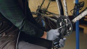 Nahaufnahme schoss von den starken männlichen Händen in den Schutzhandschuhen, die das gebrochene Fahrradpedal reparieren, das Ge stock footage