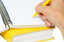 Nahaufnahme schoss von der Hand mit Feder auf gelbem Copybook. Lizenzfreies Stockbild