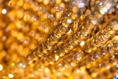 Nahaufnahme schoss von der Kristallleuchterdekoration mit goldenem Licht Stockfoto