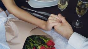 Nahaufnahme schoss von der männlichen Hand, die weibliche Hand auf Tabelle mit Champagnergläsern und -blumen hält und zusammendrü stock video footage