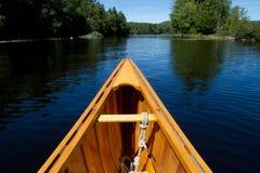 Nahaufnahme schoss von einem hölzernen Kanu auf einem Fluss Stockfotografie