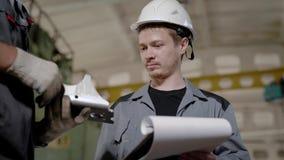 Nahaufnahme schoss von Vorarbeiterleitinspektion auf Anlage und betrachtete die Qualität von Metalldetails stock video footage