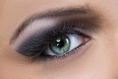 Nahaufnahme schwarzen und purpurroten glittery smokey Auges Stockbild